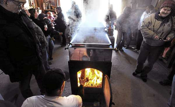 Visitors look on as Chris Getchell (bottom) loads wood into the firebox of the evapotator while making maple syrup at the Auger Hill Farm in Marshfiled Sunday.  Owner Walter Getchel said that it is hectic to open the farm to the public on Maine Maple Sunday but it is also a lot of fun.  This is more like a social event and a reason to hang out together said Chris Getchell who helps out his uncle during the maple syrup season.