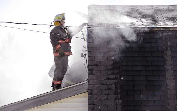 Winterport Fire Chief Tom Doe looks for trouble spots on the roof as fellow firefighters from Winterport, West Frankfort, Franfkfort Village and Monroe doused flames at the Rancourt family home on Pineview Drive in Winterport early Sunday afternoon, March 27, 2011. Samantha Rancourt said she was in Bangor running errands when the fire broke out and hurried back when she heard the news. Six of her children were at home with a babysitter and safely exited the home and went to  neighbor Ruth Morill's home Sunday afternoon.