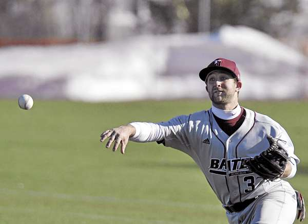 Snow lined the outfield fence, but baseball was played at Winkin Complex as Husson University hosted Bates College of Lewiston on Monday. Bates infielder Noah Burke gathers up a sharply hit ball and fires to first base in the fifth inning of their game Monday. Bates won 7-5 in 10 innings.
