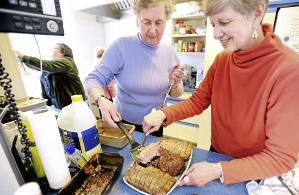 Leta Mathews (left) and Nancy Ives prepare meatloaf before the Downeast Table of Plenty free community supper at the Maine Seacoast Mission in Millbridge Sunday. They were among the members of the Cherryfield Congregational Church who provided the food for the supper.  About eight groups cook the meals for the community meal that started four months ago.  50-80 people usually attend.
