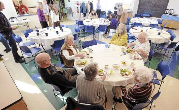 The first of the guests sit down to eat during the Downeast Table of Plenty free community supper at the Maine Seacoast Mission in Millbridge Sunday.