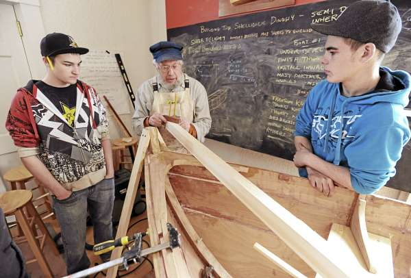 Searsport High School students Jason Pendleton (left) and Alex Lane (right) listen as wooden boat builder Greg Rossel (center) explains how a simple handcrafted tool can help them to draw a cutting line on what will be a spar as the pair, along with several other students, learns how to build a shellback dinghy at the Penobscot Marine Museum on Monday.