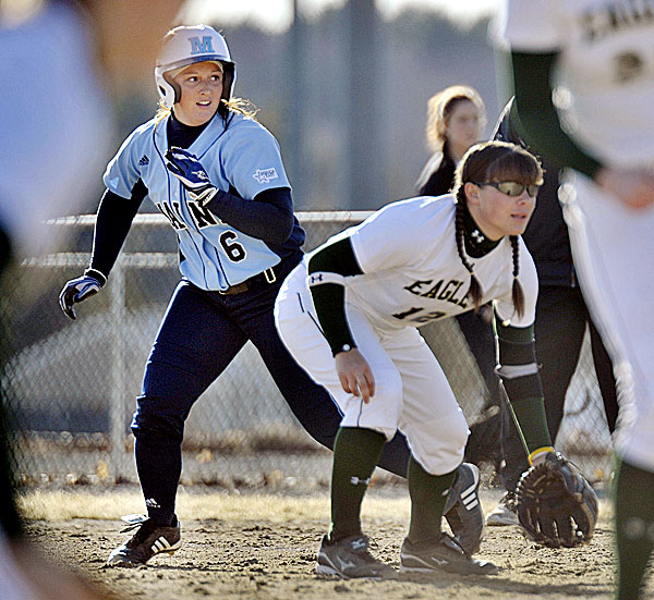 Terren Hall (left) of the University of Maine softball team takes a lead off first base behind Husson's Megan Richard in the fifth inning of Tuesday afternoon's game at Husson's Winkin Complex in Bangor. UMaine won 6-0.