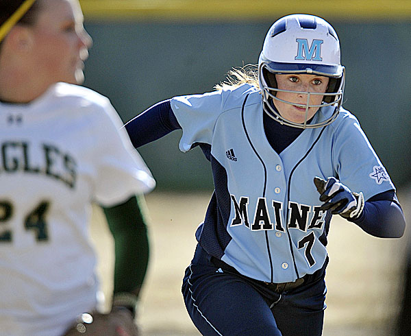 The University of Maine's Lindsey Jenkins races to third base on a passed ball during the third inning of Wednesday's college softball game against Husson University in Bangor. Husson University shortstop Diann Ramsey looks on. Maine won 6-0.