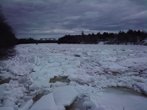 A big ice jam caused water levels to rise on the Mattawamkeag River, roads to wash out, and basements and yards to flood Saturday night and Sunday. Officials were also worried about ice damaging surrounding bridges, like the railroad bridge in the distance.