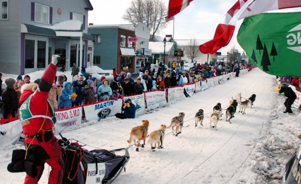 Jason Barron of Lincoln, Mont. encourages the crowds lining both sides of Main Street in Fort Kent at the start of the Can-Am Crown International Sled Dog Race in 2009.