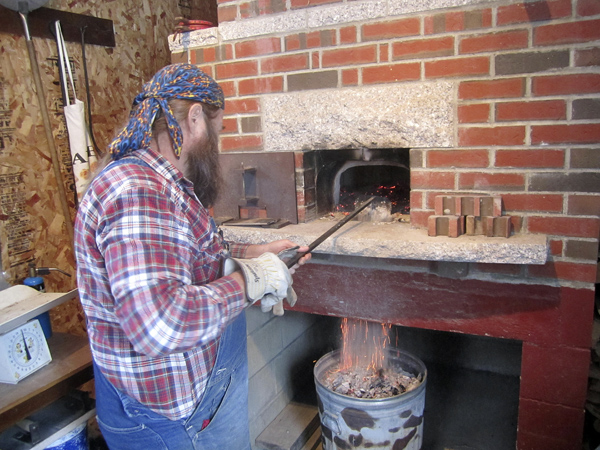 Dusty cleans coals out of his wood-fired bread oven before baking.