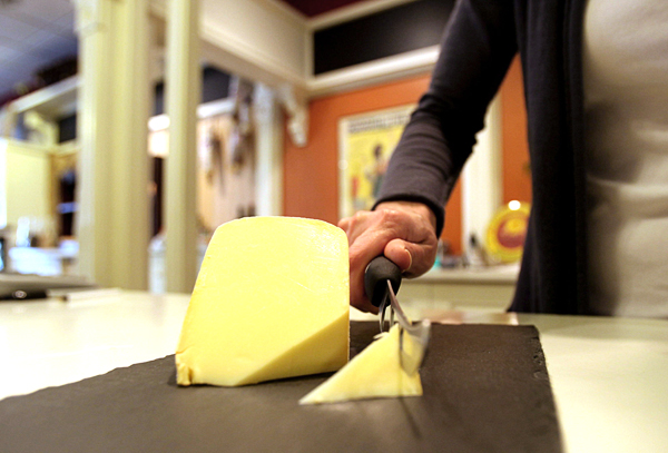 Erika Aylward, co-owner of the Boulevard Market, cuts a piece of raw milk gouda cheese at her store in Tecumseh, Michigan.