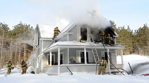 Firefighters work to extinguish a fire at a residence on Summer Street in Lisbon Falls, Maine, Friday morning, March 4, 2011. The state fire marshal's office said two sisters died in the home when they were trapped in a bedroom. Their mother was treated for smoke inhalation and burns that she suffered when she tried to save them.