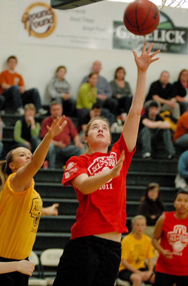 A-B East's Megan Phelps, MDI H.S., takes a shot as A-B West's Keila Grigware defends during the 2011 Maine McDonald's High School All-Star basketball games at Husson University on Saturday.