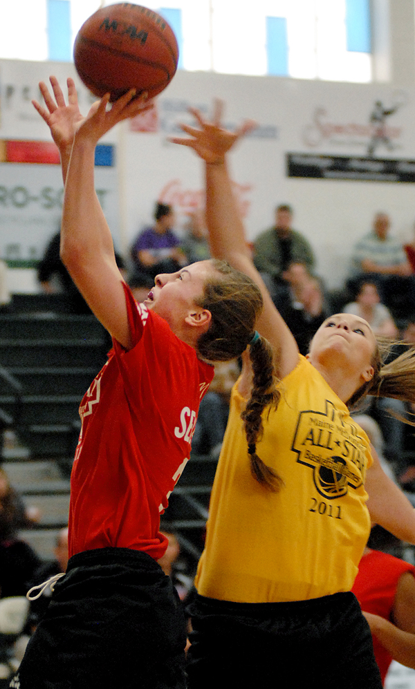 A-B West's Keila Grigware, Biddeford H.S.,fouls A-B East's Jenna Selander, Caribou H.S., as she goes up for a shot during the 2011 Maine McDonald's High School All-Star basketball games at Husson University on Saturday.