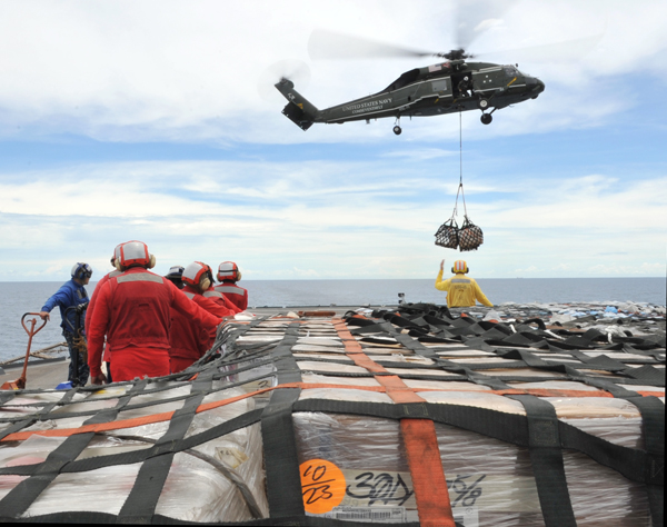 U.S. Navy, sailors aboard the U.S. 7th Fleet command ship USS Blue Ridge (LCC 19) in the South China Sea stand-by to move pallets of humanitarian relief supplies across the ship's flight deck during an underway replenishment with the Military Sealift Command fleet replenishment oiler USNS Rappahannock (T-AO 204), not pictured. Blue Ridge is ensuring the crew is ready if directed to assist with earthquake and tsunami relief operations in Japan.