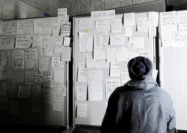 A resident looks at a message board at an evacuation center in Ofunato, Iwate prefecture, Saturday, a day after one of Japan's strongest earthquakes ever recorded hit the country's east coast.