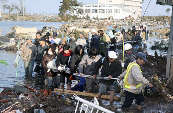 People who were isolated at an elementary school, head for safety place in Sendai, northern Japan Saturday after one of the country's strongest earthquakes ever recorded hit its eastern coast on Friday.