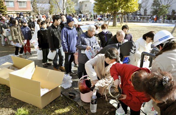 Local residents form a long line at a water station set up at a park at Koriyama, northeastern Japan, on Saturday, one day after a giant quake and tsunami struck the country's northeastern coast.