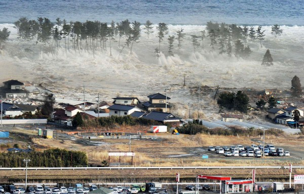 Waves from a tsunami hit residences after a powerful earthquake in Natori, Miyagi prefecture, Japan, Friday, March 11, 2011.  The largest earthquake in Japan's recorded history slammed the eastern coast Friday.