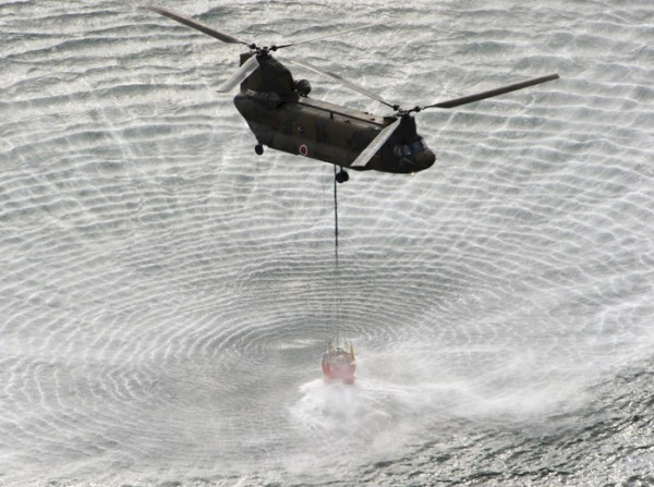 Japan's Self-Defense Forces's helicopter scoops water off Japan's northeast coast on its way to the Fukushima Dai-ichi nuclear power plant in Okumamachi Thursday morning, March 17, 2011. Helicopters are dumping water on a stricken reactor in northeastern Japan to cool overheated fuel rods inside the core.