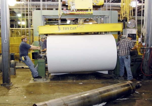 Workers at Lincoln Paper and Tissue LLC of Lincoln move a giant roll of paper onto a machine at the mill on March 11, 2011. The U.S. Department of Labor's Occupational Safety and Health Administration on Wednesday announced that it is seeking $212,000 in fines from the papermaker for alleged unsafe work conditions.