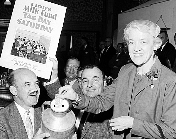 Senator Margaret Chase Smith donates to the Bangor-Brewer Lions Club school milk fund during her visit to the Queen City Wednesday to address a joint service club meeting. Holding the milk can are Lions Rudolph Marcoux and George Toulas.