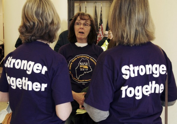 Dorothy Eaton (center) of Augusta talks with Cathy Green (left) of Winslow and Betty Wilkins (right) of Hallowell, all state workers, during a rally at the State House in Augusta, Maine, on Wednesday, March 2, 2011. Union members upset with the  governor's  proposals to change the pension system gathered at the State House.