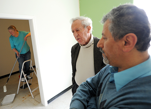 Dr. Peddie (center), and Pharmacist Ali Aghamoosa (right), talk with a reporter as Pam Peddie (left), wife of Dr. Peddie, paints a room which will be Dr. Peddie's personal office at the Orono Pharmacy on Mill Street in Orono on Thursday.