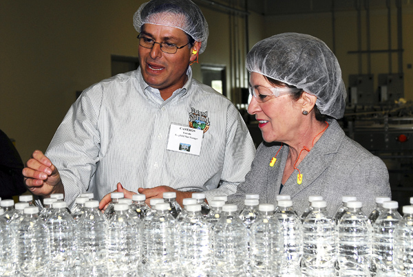 Sen. Susan Collins and Cameron Cameron Lorrain, plant manager of Poland Spring's Kingfield plant, watch as bottles zip by, heading for the labeling machines on Wednesday.