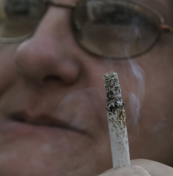 A woman smokes a cigarette outside a smoke shop in Lewiston in 2007. A Wilton lawmaker had proposed to deny MaineCare benefit to smokers, but revised the legislation after sensing opposition.