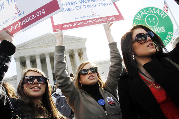 Kenzie Harvison (rom left), 17, Sarah Rollison, 17, and Dorothy Bullard, 17, in Washington for a leadership conference from their boarding school in Arizona, take part in rally outside the Supreme Court in Washington, Tuesday in support of the plaintiffs in a case of women employees against Wal-Mart.