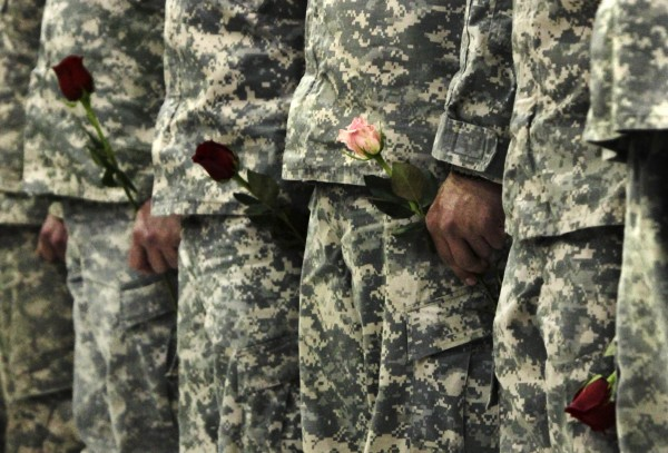 Members of the 1136th Transportation Company of the Maine National Guard hold roses before being dismissed upon their return home to Augusta, Maine, on Tuesday, March  8, 2011, after spending almost a year in Afghanistan.