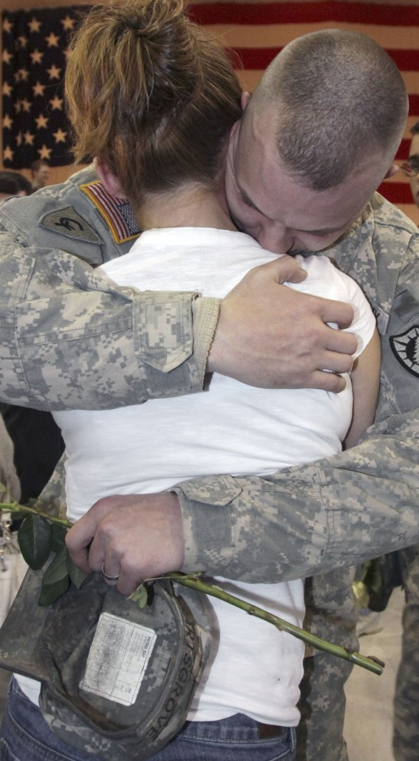 Joshua Hartsgrove is greeting by his wife, Heidi, both from St. Albans, Maine, upon his return on Tuesday, March  8, 2011, with members of the 1136th Transportation Company of the Maine National Guard in Augusta, Maine, after spending almost a year in Afghanistan.