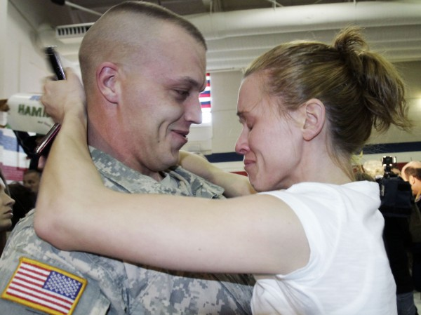Joshua Hartsgrove is greeted by his tearful wife, Heidi, both from St. Albans, Maine, upon his return on Tuesday, March 8, 2011, with members of the 1136th Transportation Company of the Maine National Guard to Augusta, Maine, after spending almost a year in Afghanistan.