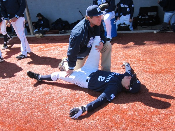 University of Maine sophomore Michael Fransoso (on ground) receives some stretching help from trainer Phil Watson prior to the first game of Saturday's doubleheader in Jersey City, N.J.