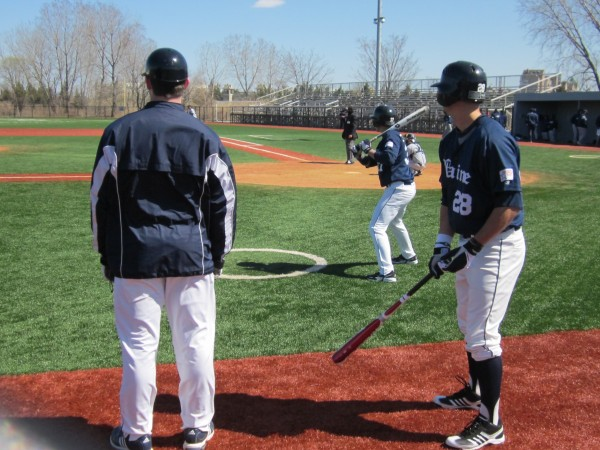 University of Maine assistant coach Bill Cather (left) and players Pat Thibodeau (background) and Joe Martin size up the St. Peter's pitcher during Saturday's game in Jersey City, N.J. The Peacocks won 7-5.