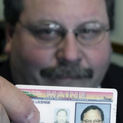 Rep. Richard Cebra, R-Naples, holds up his driver's license in his office at the State House in Augusta, Maine, on Tuesday, March 1, 2011. Cebra is a co-sponser of a Maine proposal that would require voters to show photo identification at the polls.