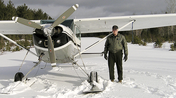 Daryl Gordon stands next to a plane (not the one in which he crashed) on a frozen lake in 2007.  Gordon, one of the agency's game wardens, was killed in the crash of a small plane on Clear Lake in a remote northern part of Piscataquis County Thursday night.