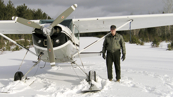 This January 2007 photo released by the Maine Department of Inland Fisheries and Wildlife shows Daryl Gordon standing next to a plane on a frozen lake.