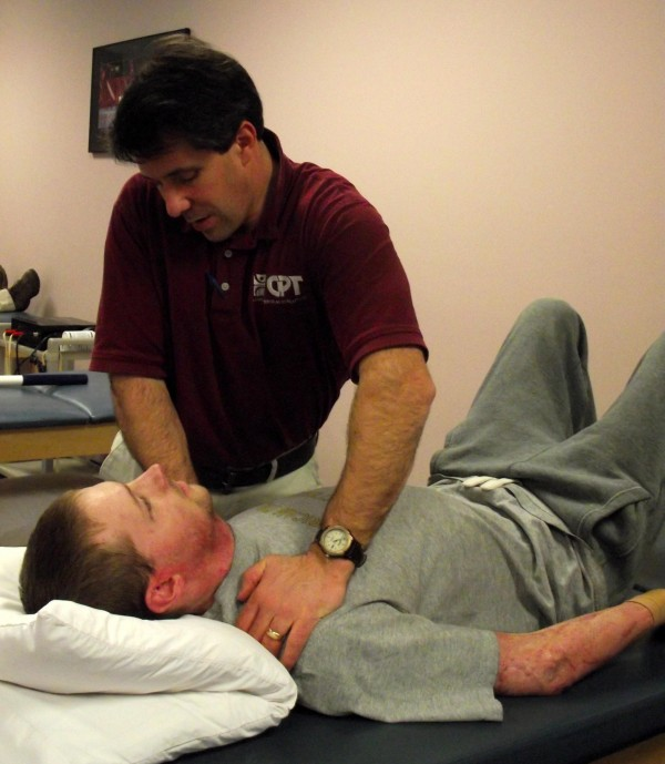 Paul Marquis (standing), physical therapist and vice president of clinical operations at County Physical Therapy in Presque Isle, works with Zane Wetzel of Mars Hill on stretching and manipulation exercises in March 2011.