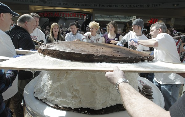 "Amy Bouchard, owner of Wicked Whoopies (fourth from right), gets help putting the 180 pound devils food cake top on the 1000-plus pound whoopie pie at the Maine Mall in South Portland, Saturday.  Competing with Pennsylvania to be the ""Whoopie Pie State"", Maine is looking to officially make the Whoopie Pie the State Treat."