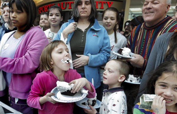 "As brother Ryan, 6 (lower right), looks on, Natalie Grondin, 9, of Falmouth is one o the first to get a taste of the 1000-plus-pound whoopie pie that was put together at the Maine Mall in South Portland Saturday.  Competing with Pennsylvania to be the ""Whoopie Pie State"", Maine is looking to officially make the Whoopie Pie the State Treat."