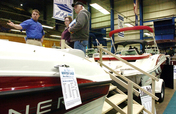 Blaine King, left, of Port Harbor Marine, shows a boat to Teresa and David Shorey of Etna at the annual Bangor Boating and Marine Show held on Saturday at the Bangor Auditorium and Civic Center. The Shoreys are starting to look into buying a boat. &quotWe came here to window shop, which always leads to temptation,&quot joked Teresa.