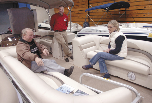 Mike Johnson and Sharon Nelson, both of Meddybemps, test the comfort of a pontoon boat's seats as Hamlin Marine's Brandon Clark looks on during the annual Bangor Boat and Marine Show on Saturday at the Bangor Auditorium and Civic Center.