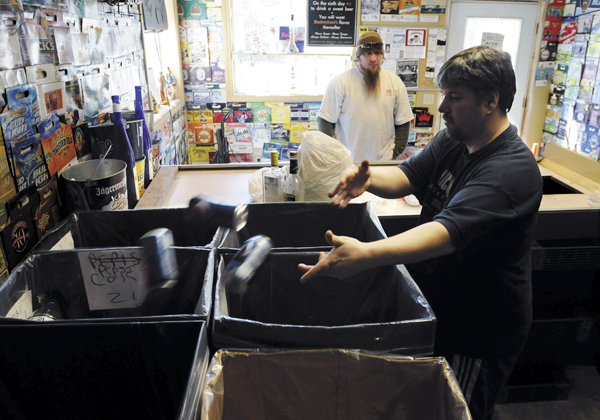 Joey Ouellette (right), owner of Skeeter's Redemption Center in Old Town, sorts bottles for customer Ryan Porter of Old Town. Ouellette does not feel that removing the 15 cent deposit on wine and liquor bottles will result in people recycling them rather than throwing them in the trash.