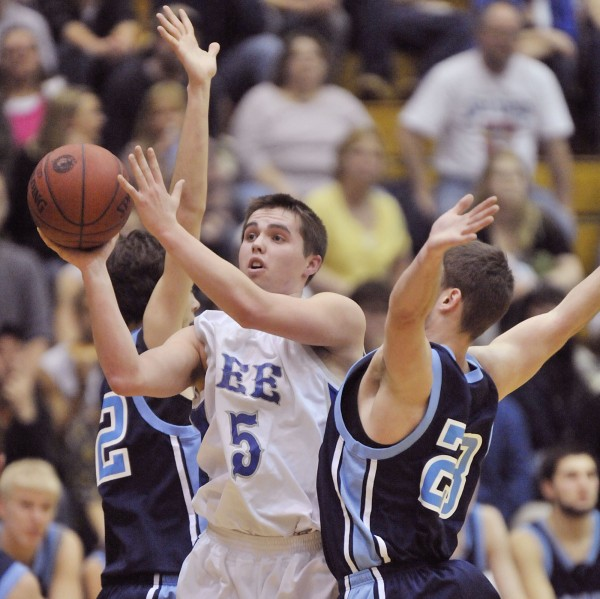 Billy Nicholas (center) of Lee Academy drives to the hoop between Ben Holmes (22) and Arik Fenstermacher (23) of Dirigo of Dixfield in the first half of their Class C state championship boys basketball game at the Bangor Auditorium Saturday. Lee won 65-55 for its first boys basketball state title.