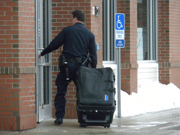 Bangor police Officer Mike Brennan wheels an equipment box into the Broadway branch of Bangor Savings Bank Saturday afternoon. Police were called to the bank to investigate a report of a bank robbery.