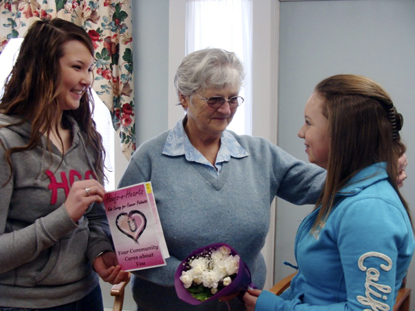 Jo-ann Gould of Wellington, who had just finished her chemotheraphy treatment at Mayo Regional Hospital in Dover-Foxcroft Wednesday, received a floral bouquet from Elaine Riitano, left, and Samantha Jo Brawn, both Piscataquis Community Secondary School pupils. The girls made the presentation to Gould the same day they donated 25, $25 gift cards to the hospital to help cancer patients such as Gould with transportation costs to and from the hospital.