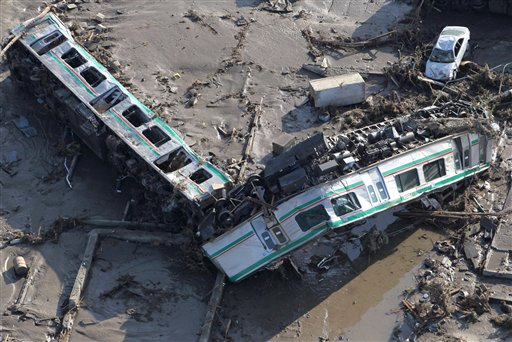Cars of a train lie overturned in Shinchi town, Fukushima prefecture, Saturday, March 12, 2011 after being washed away by an earthquake-triggered tsunami.