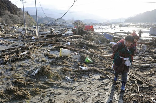 A woman, carrying a child on her back, walks over tsunami-drifted debris and mud in Rikuzentakada, Iwate Prefecture, Saturday morning, March 12, 2011 after Japan's biggest recorded earthquake slammed into its eastern coast Friday.