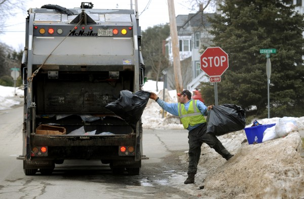 Steve Davis, an employee of Pine Tree Waste of Hermon, throws trash bags into a garbage truck in Bangor. The city is considering a pay-as-you-throw trash collection program that would require Bangor residents to puchase trash bags from the city that would be collected at the curb.