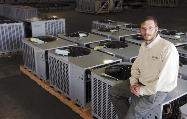 Duane Hallowell, president of Hallowell International, leans on some of the heat pumps his company manufactured in Bangor in 2009.