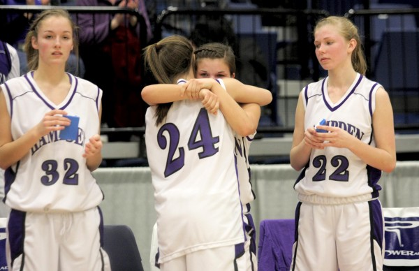 Hampden Academy's Michaela Stephenson gets a hug from Ellie Webb (24) as Jordan Maxwell, right, looks on following the Broncos' 39-23 loss to Catherine McAuley High School in the girls Class A state championship game at the Augusta Civic Center on Saturday night.